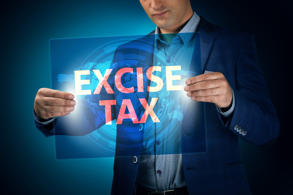 Businessman holding a transparent screen with an inscription a excise tax. Business, technology, internet and networking concept.